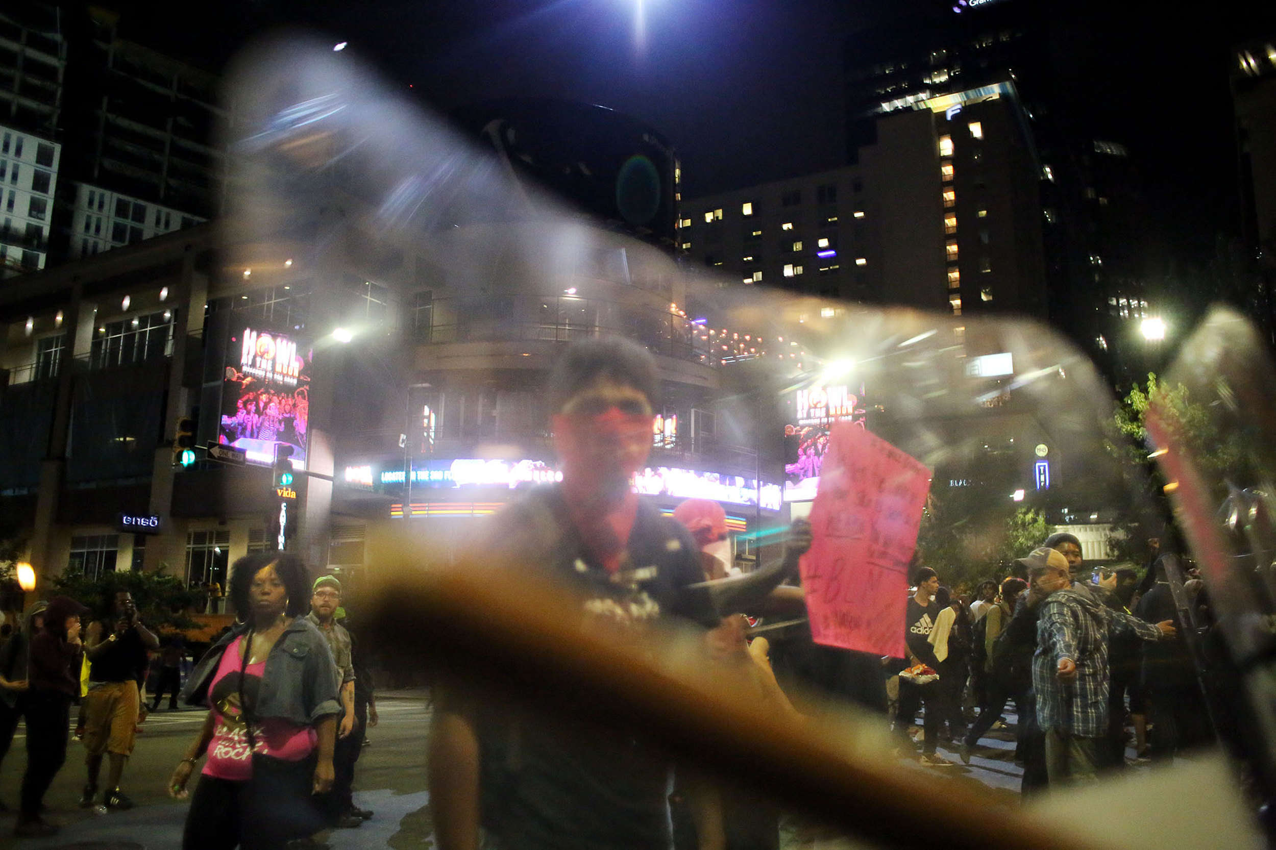 A masked protester is seen through a riot police shield, Sept. 21, 2016, at the intersection of North College and East Trade streets in downtown Charlotte, N.C.
