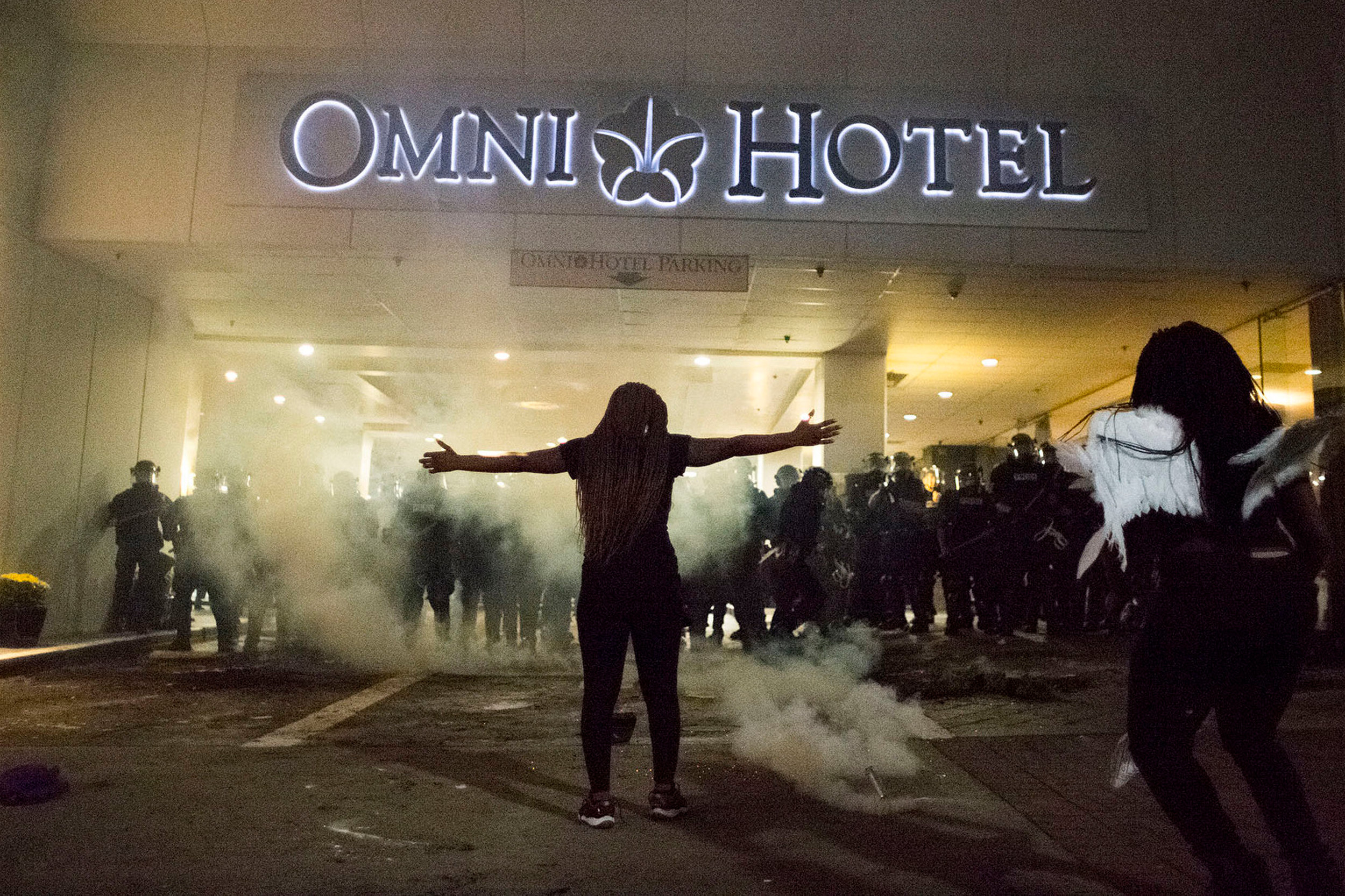 A protestor stretches out her arms as police deploy crowd control agents in front of the Omni Hotel, Sept. 21, 2016, on East Trade Street in downtown Charlotte, N.C, during the second night of clashes between police and protesters.