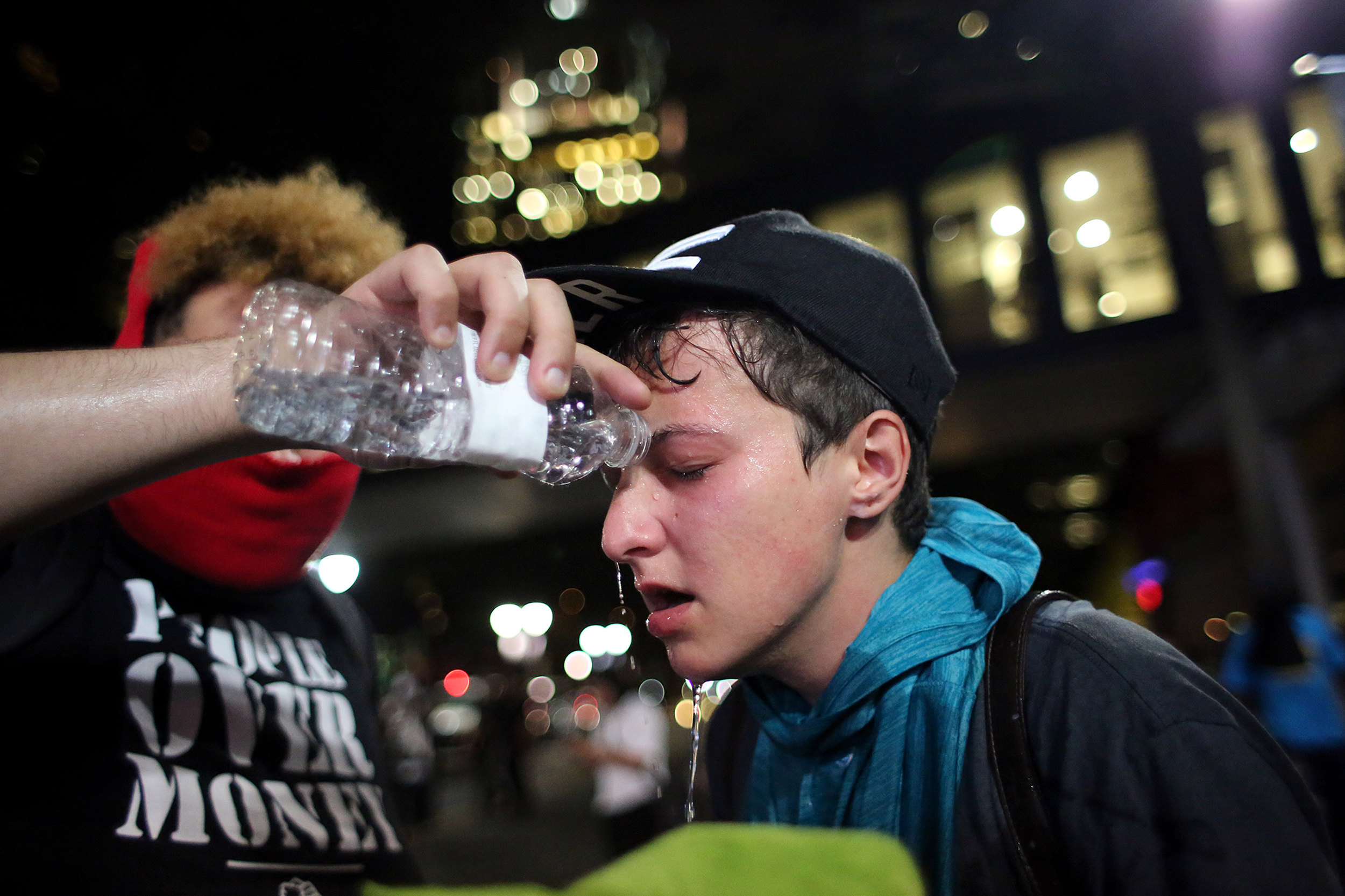 A protester douses a fellow protester's eyes with water after law enforcement deployed tear gas, Sept. 21, 2016, in downtown Charlotte, N.C.