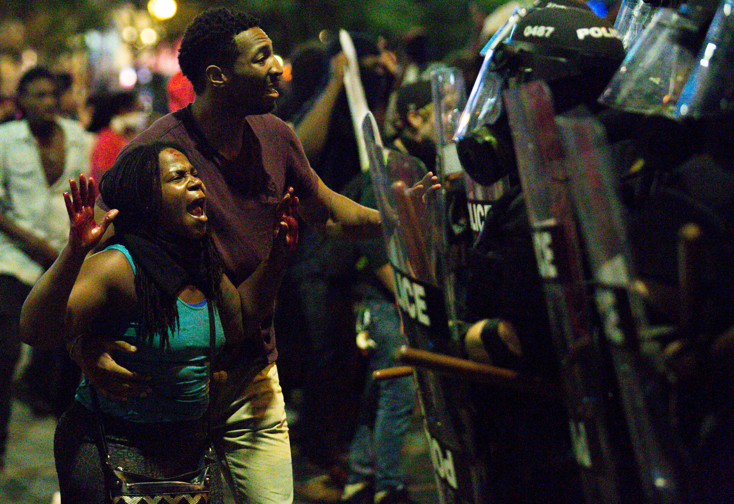 A protester with blood on her hands shouts at riot police officers immediately after a shooting in the crowd left a protester critically injured, Sept. 21, 2016, at the intersection of North College and East Trade streets in downtown Charlotte, N.C. Justin Carr, 26, who was allegedly shot by another protester, Rayquan Borum, 21, later died from his injuries.