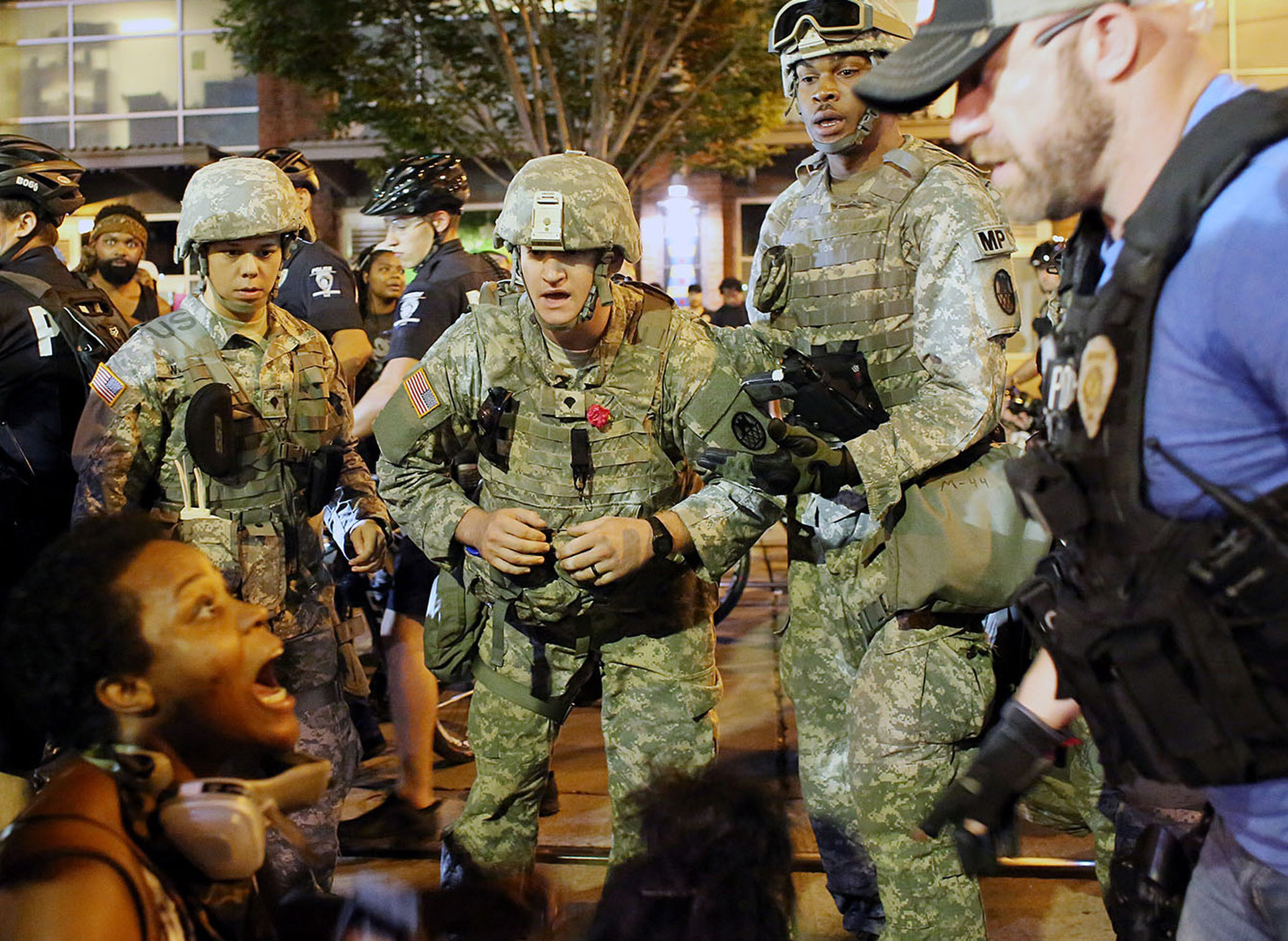 Members of the North Carolina National Guard and police officers attempt to assist a protestor having a medical emergency, Sept. 22, 2016, on East Trade Street in downtown Charlotte, N.C. The protester declined assistance.