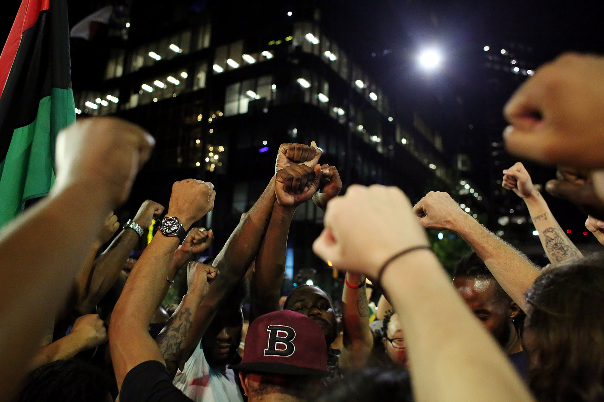 Protesters raise their fists together during a pause in a protest march, Sept. 22, 2016, in downtown Charlotte, N.C.