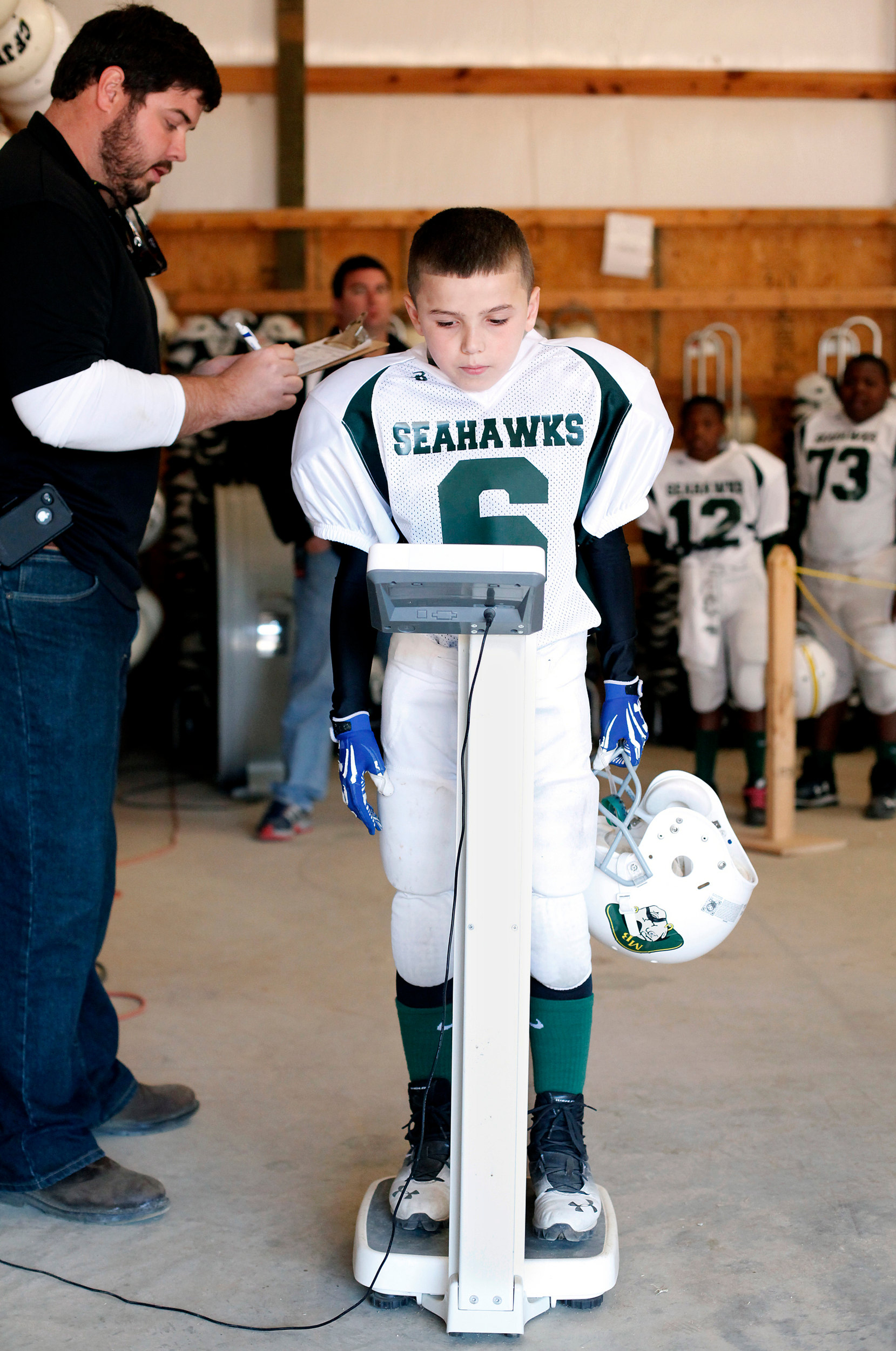 The Myrtle Beach Seahawks' Anthony Aponte, 10, has his weight checked by Matt Watts (left) on Saturday, Nov. 15, 2014, at Freedom Florence Recreational Complex.