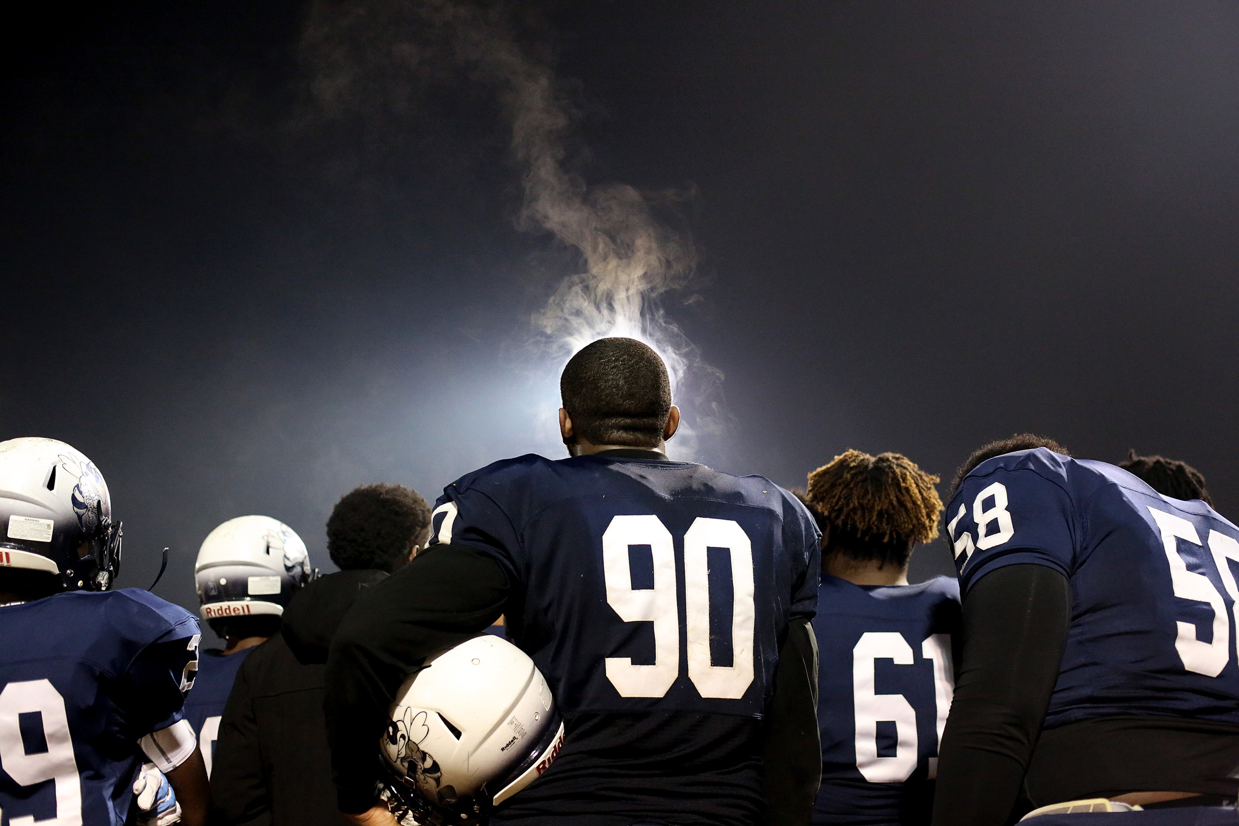 Steam rises from the head of Hillside High School's David Gray, center, as he and teammates huddle during halftime of a Class 4A playoff game against Hoggard High School, Nov. 18, 2016, at Hillside High School's Russell E. Blunt Stadium in Durham, N.C. Hoggard won, 38-34, ending Hillside's season.