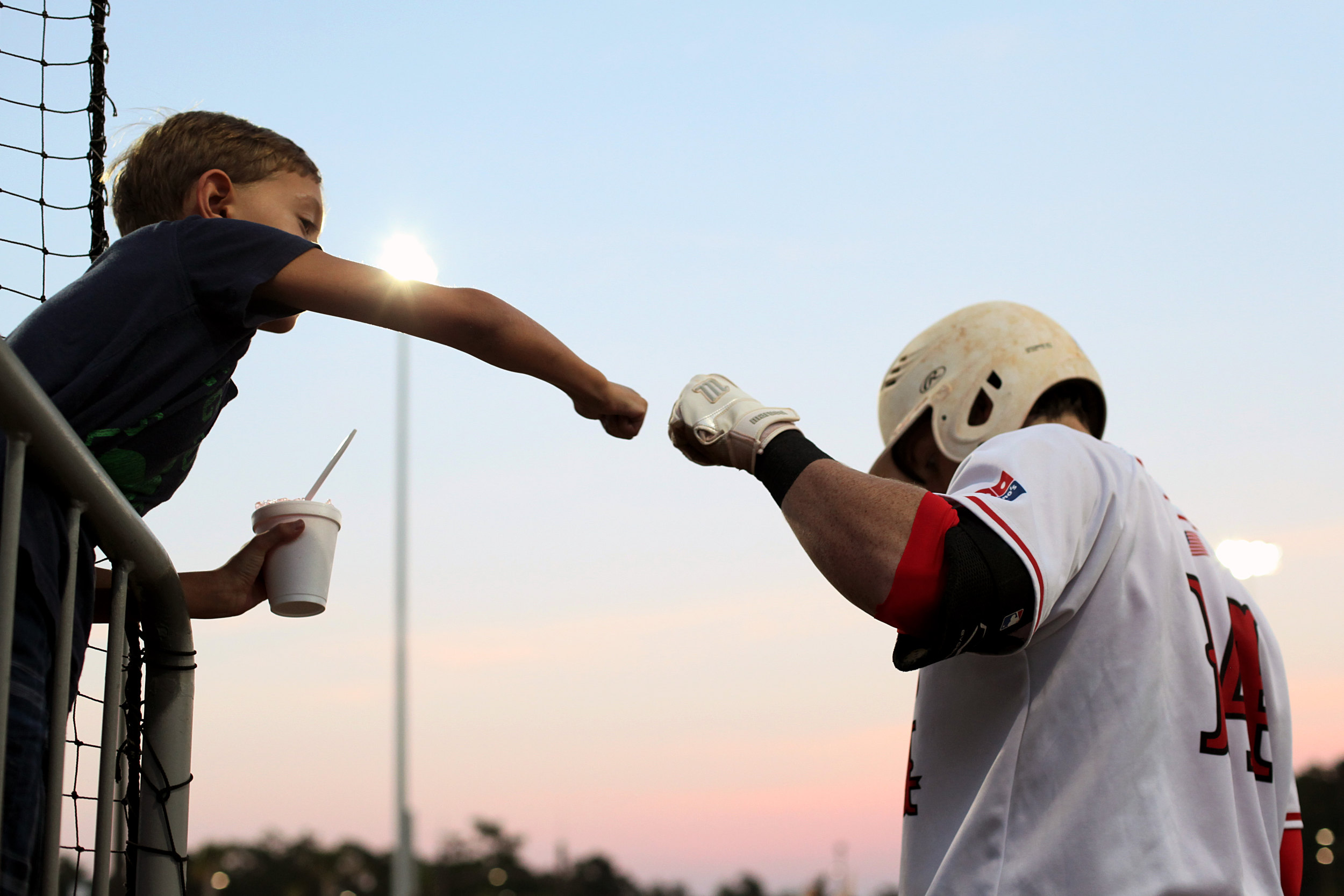 A Florence RedWolves fan fist-bumps the RedWolves' Brandon Rawe as he steps out of his team's dugout. The RedWolves beat the Peninsula Pilots, 4-1, in the first game of the Petitt Cup Championship Series on Thursday night, August 14, 2014, at Sparrow Stadium in Florence, S.C.