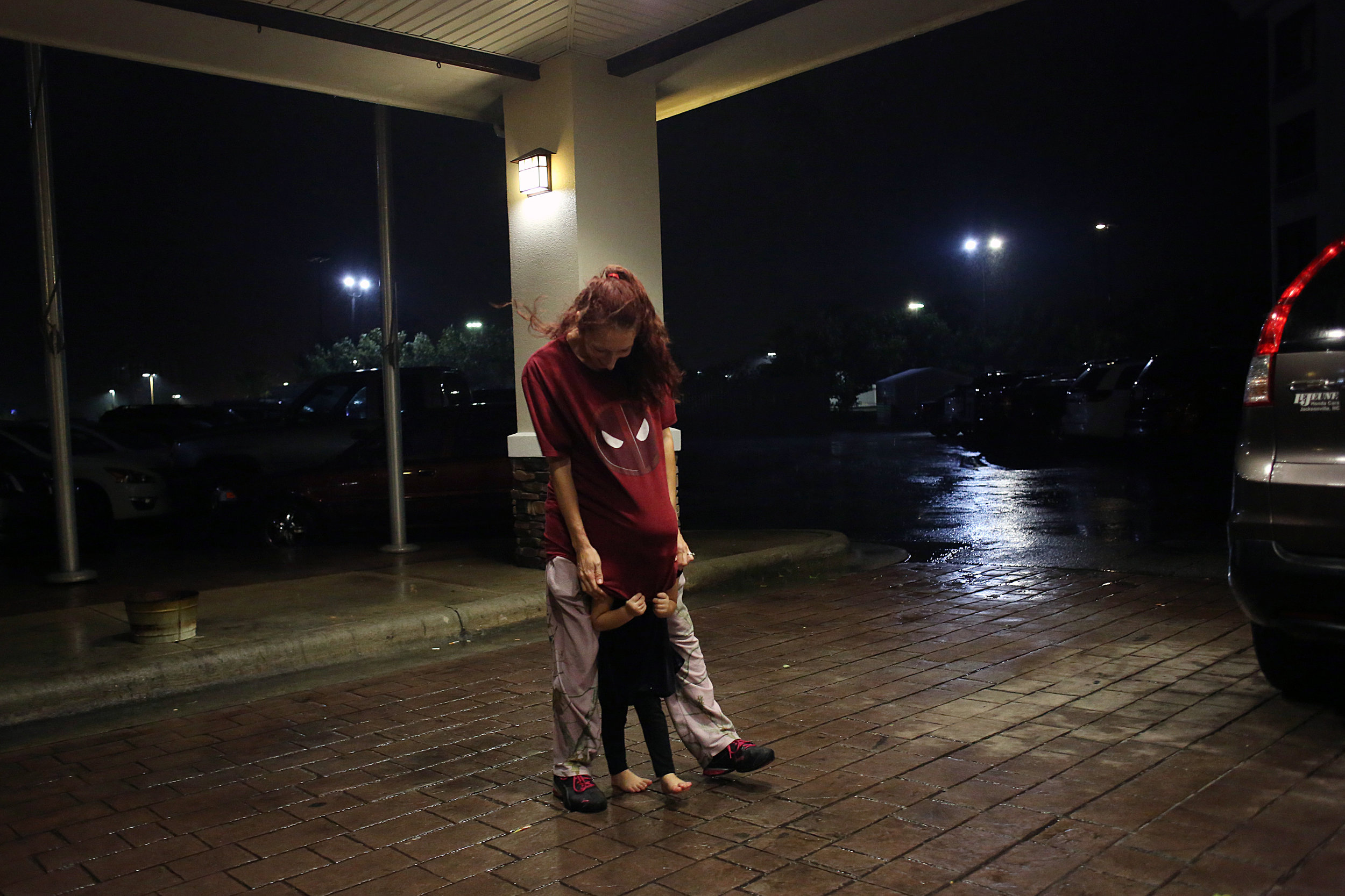 "Allana Bailey, of Hubert, plays with her daughter, Brooklynn Lowe, 3, outside of the Holiday Inn Express as Hurricane Florence rolled in, Sept. 13 in Jacksonville, N.C. ""They're tired of being cooped up in the room -- but they've got a pocketful of energy,"" Bailey said of her twin daughters, who she calls 'twinados'."