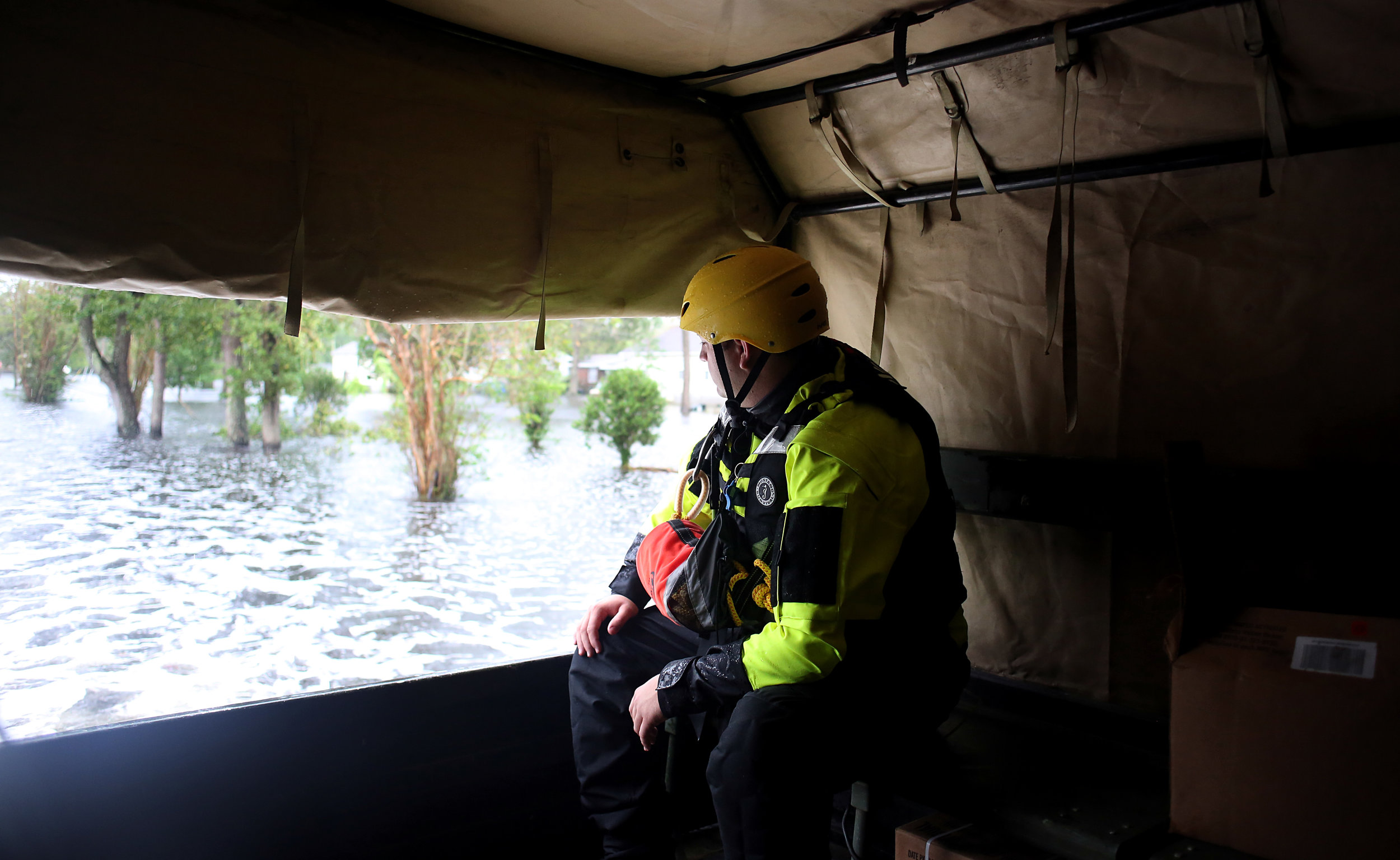 A member of North Carolina Task Force 10 looks out at floodwaters from the back of a national guard LMTV as a mixed unit of guardsmen and rescue personnel conducted welfare checks, Sept. 15 in New Bern, N.C.