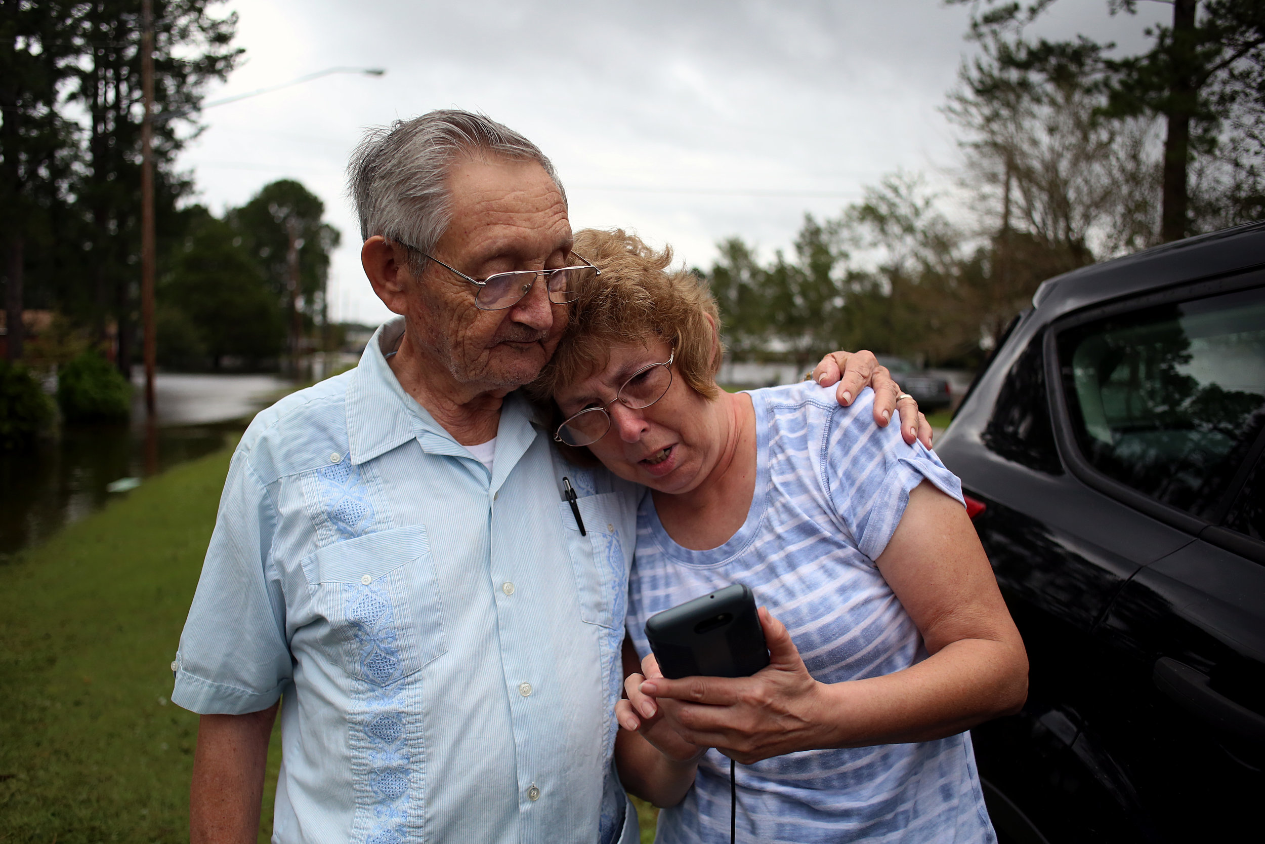 Cleo Jones, 85, embraces Annette Jones Kennedy outside his flooded home on Simmons Street as she shows him photos of her own flooded home, Sept. 15 in New Bern, N.C.