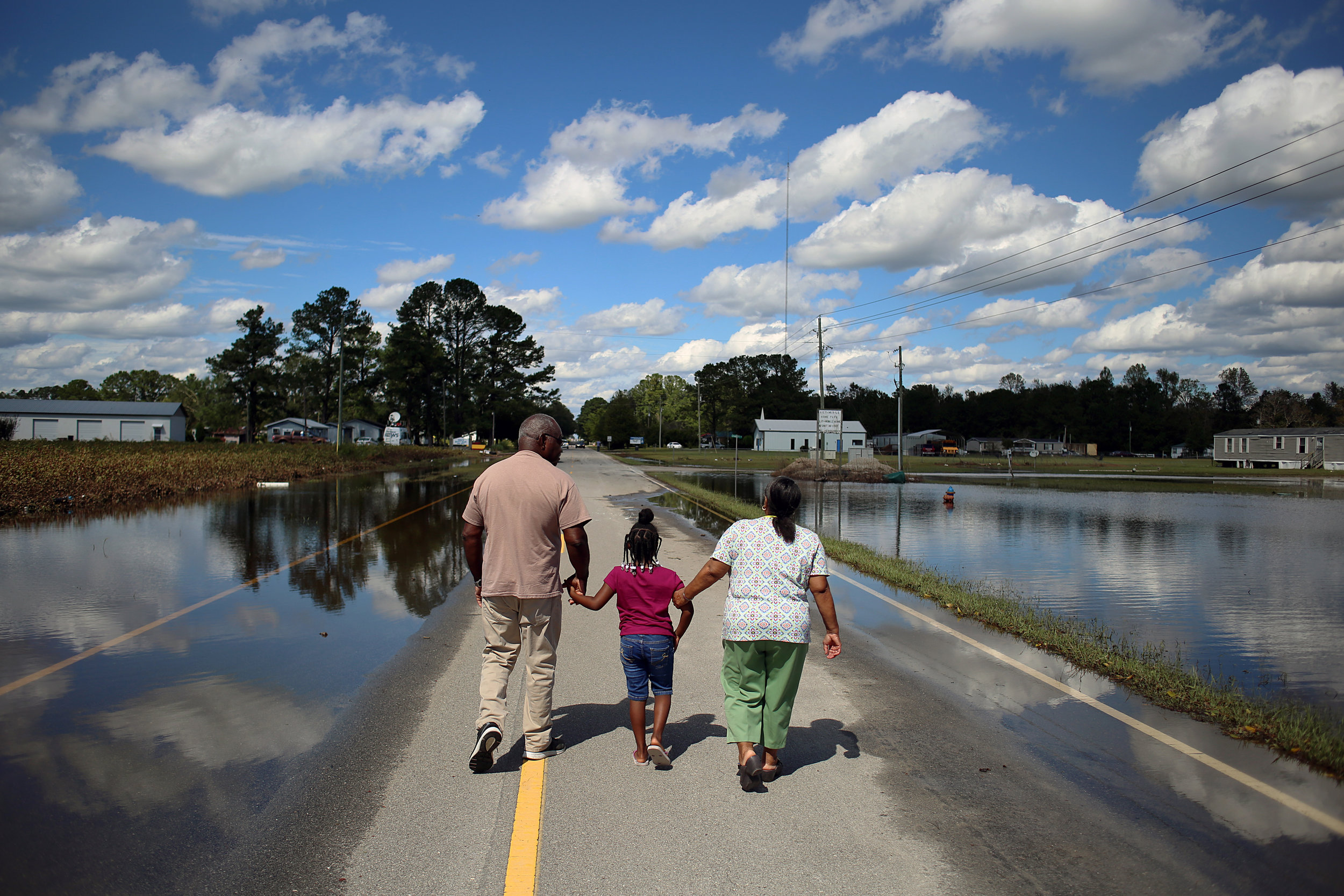 "Allen Chapman, 71, Fannie Chapman, 72, and their granddaughter, Maryah Chapman, 7, walk down Highway 41 after viewing their flooded home, Sept. 18, in Trenton, N.C. ""We've been here 51 years on this street,"" Fannie said. ""This is our first time back since it happened. It flooded in '99, but not like this. It's gone again."" Allen Chapman vowed to persevere, but wasn't confident in FEMA's disaster assistance, and wondered how people were even able to pay for flood insurance. ""Out here, we're low on the totem pole,"" he said. ""It ain't gonna happen overnight."" The water was too deep for Allen to make it into his home, but he know it was a total loss. ""You're looking at what I got,"" he said. The family evacuated to Raleigh for the storm."
