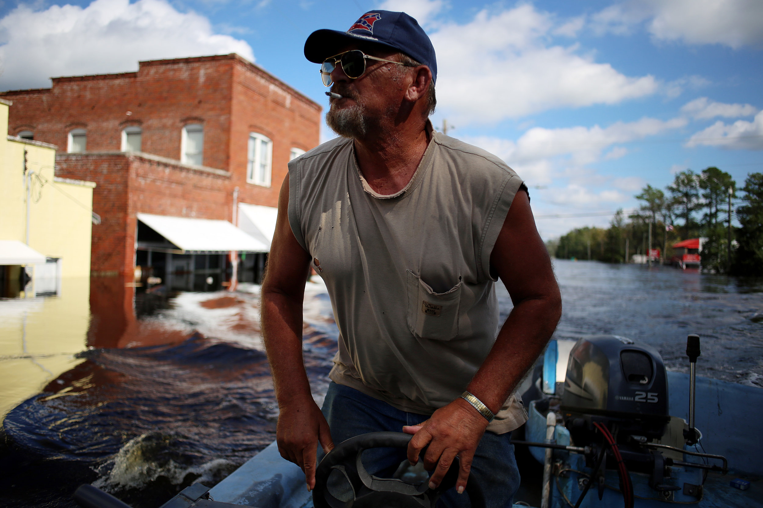 "Donald Jones, of New Bern, guns his boat down Main Street, which was flooded by the nearby Trent River, Sept. 18, in Pollocksville, N.C. Jones was helping deliver food and water for Kim Arthur, whose home was in an area largely cut off from outside resources. ""I'm about 10 minutes out in the country and this is the only way to get to town,"" she said."