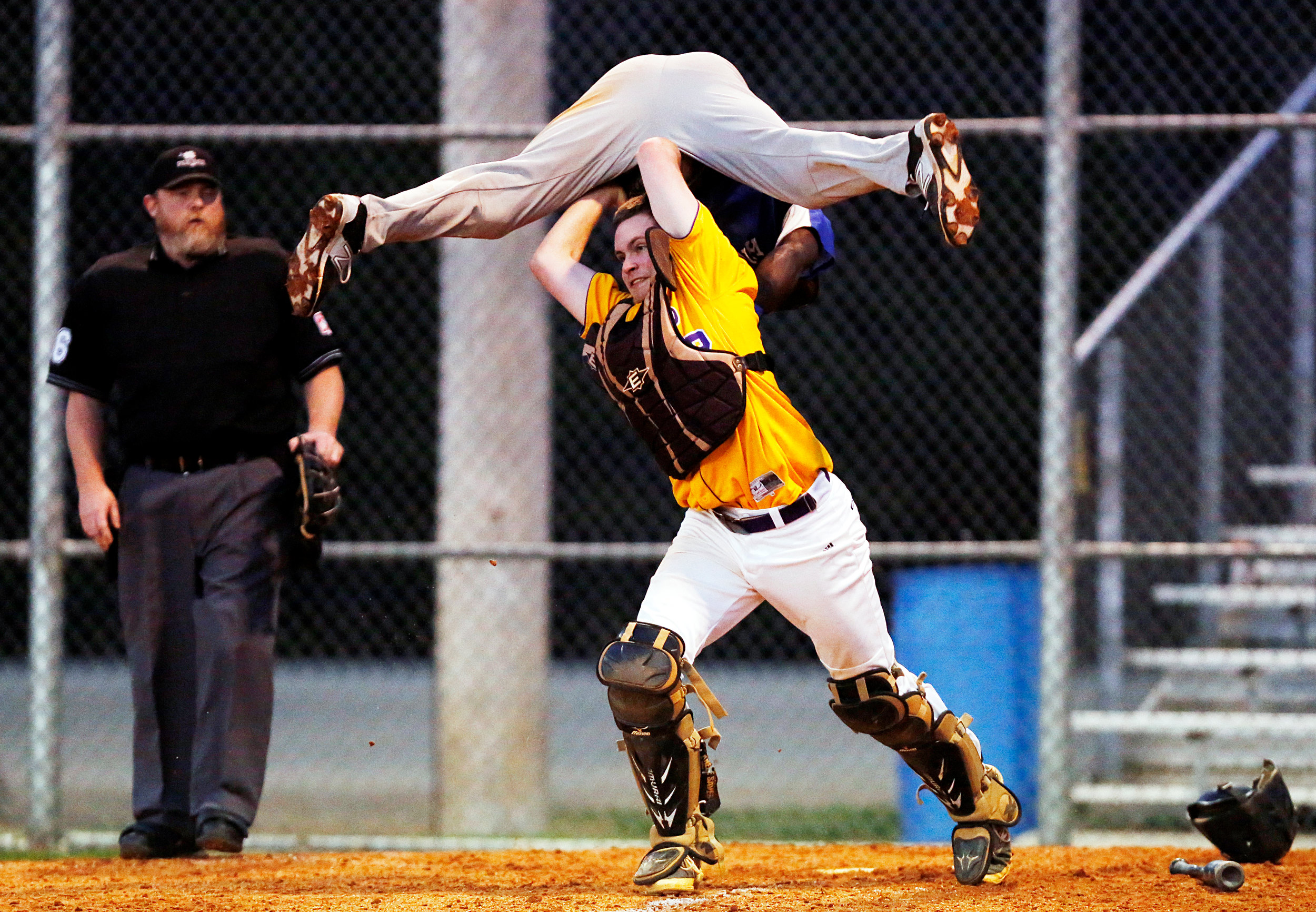 Lake City High School's Keenan Graham, top, is tagged out -- and upended -- by Wilson High School's Mason Park as he tries to hurdle his way to home plate. Lake City took on Wilson on Tuesday night, March 17, 2015, at Wilson High School. Lake City won, 5-2.