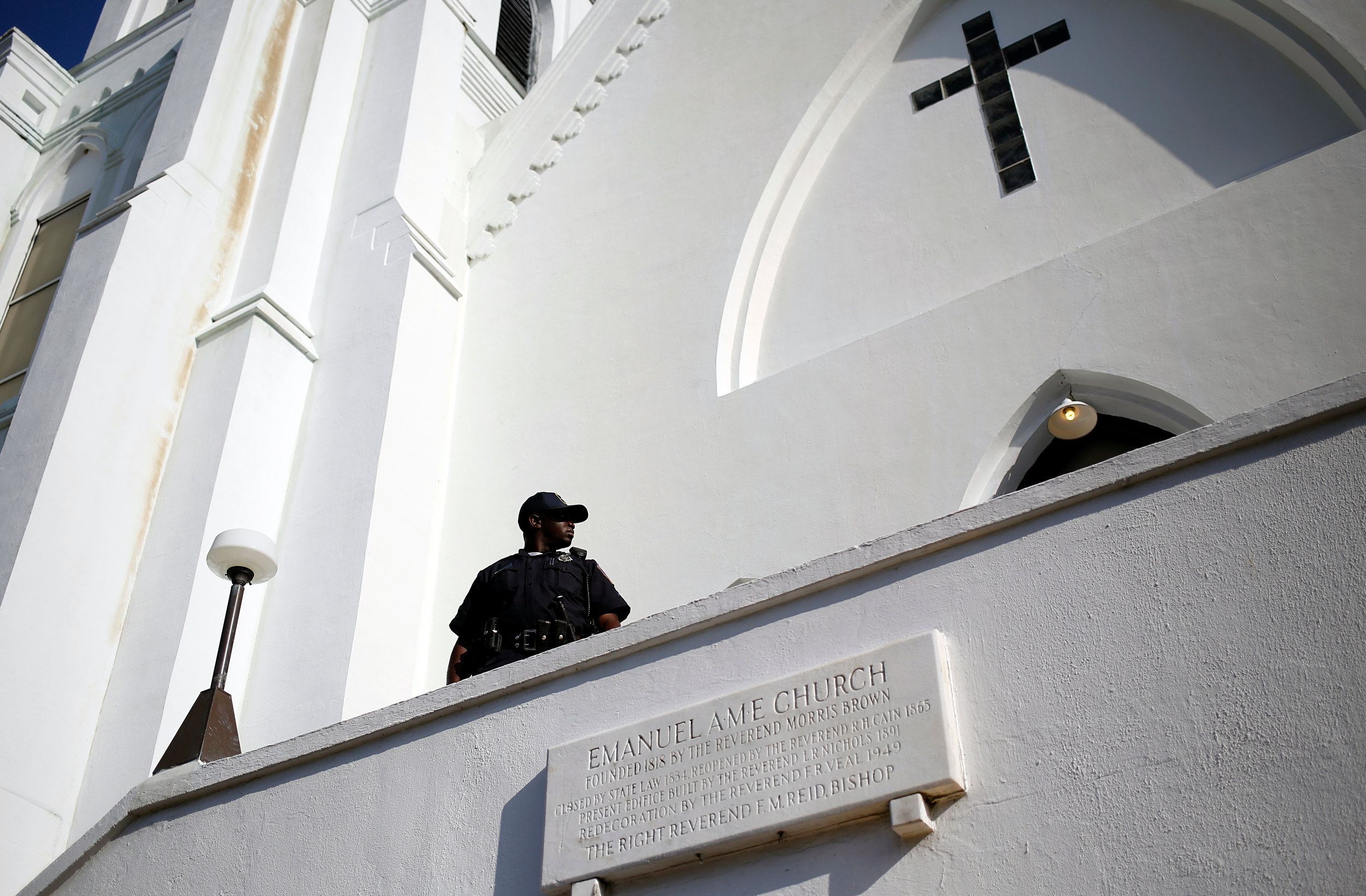 A police officer keeps watch at the entrance to the Emanuel African Methodist Episcopal Church as a worship service took place inside, four days after a shooting by Dylann Roof left nine black churchgoers dead, Sunday, June 21, 2015, in Charleston, S.C.