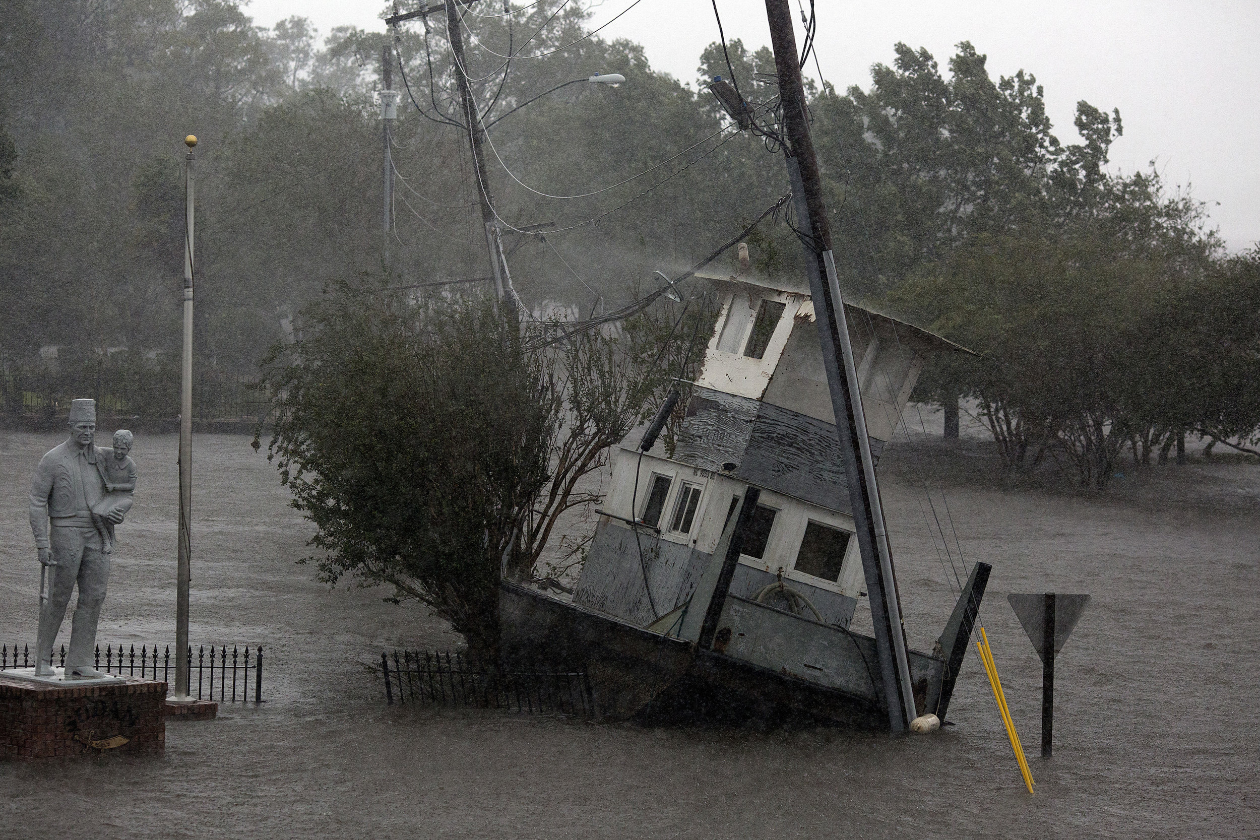A tugboat, pushed ashore from the nearby Neuse River by the storm surge, is seen Sept. 14 in downtown New Bern, N.C. as rain continued to fall.