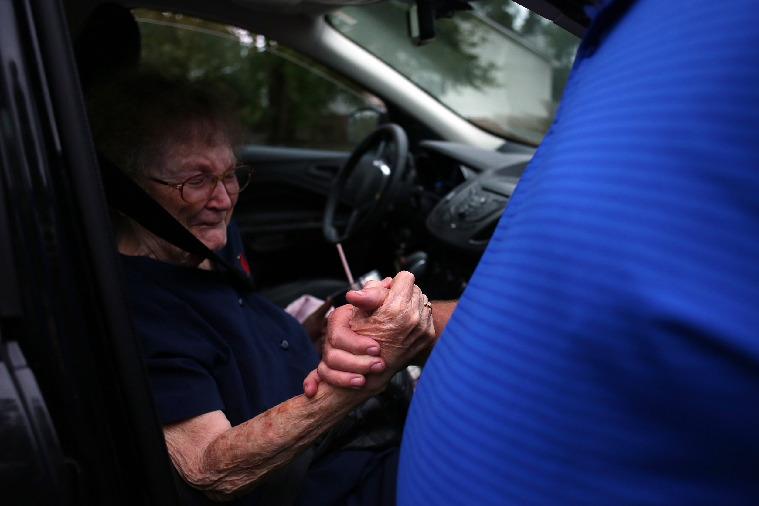 "Elizabeth Jones, 83, clasps the hand of her neighbor David Morgan outside of their homes on Simmons Street in New Bern, which were flooded. They had returned during a lull to retrieve belongings. ""You see this stuff on TV,"" Mr. Morgan said. ""You don't really know devastation until it happens to you."" The water came in as they were sleeping, Morgan said, and they had to leave in a hurry. 'Just didn't have time to grab more stuff,' he said, adding, ""We learned a lot from this."" Ms. Jones, who had been evacuated by the National Guard, said, ""I never dreamed this would happen."""