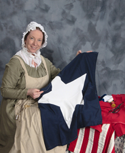 """Mary Pickersgill PORTRAYED BY KIM HANLEY - In the summer of 1813, Baltimore seamstress and widow, Mary Young Pickersgill was commissioned to make two flags for Major George Armistead, the Commandant of Fort McHenry. One was a smaller foul-weather flag measuring 17′ x 25′ and the other, a very large 42′ x 30′ fair-weather banner. Daybreak on September 14, 1814, the morning after the British bombardment of Fort McHenry, Francis Scott Key saw this larger flag in the """"dawn's early light"""", inspiring him to write the words that would become the United States' National Anthem. That very same Flag is still in existence, and remains one of our Nation's most important and beloved artifacts, viewed my millions of visitors every year at the Smithsonian Institution's National Museum of American History.In her later years Mary Young Pickersgill became a great supporter of humanitarian causes in Baltimore, particularly those dealing with indigent widows. Today, the Pickersgill Retirement community which bears her name, continues to help senior citizens in needMeet Mary Young Pickersgill, the plucky widow who literally sewed the fabric of our Nation's history.""""We, sir, are ready at Fort McHenry to defend Baltimore against invading by the enemy . . . except that we have no suitable ensign to display over the Star Fort, and it is my desire to have a flag so large that the British will have no difficulty in seeing it from a distance.""""Major George Armistead, Commandant of Fort McHenry, July 1813Mary Young Pickersgill Program Categories:Meet & Greets, Chautauquas, Libraries, & other adult & family venues,Grade School & Middle School Aged Audiences"""