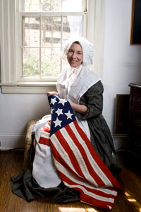 "Betsy Ross PORTRAYED BY KIM HANLEY - Elizabeth Griscomb Ross Ashburn Claypoole's story differs from, and is superior to, the myths that enshroud her true legacy. Hers is the story of a strong and independent woman who was willing to work hard and follow her own mind and heart at a time when women were expected to conform to tradition. When she was 14 she began an apprenticeship in the upholsterers' trade. At the age of 21 she married against her Father's wishes and outside of her faith, resulting in her being ""read out of meeting"", and losing the support of her Quaker meeting house. Her husband died in January, 1776, as the movement for independence was gaining intensity. She struggled to maintain her business and patriotic beliefs during the British occupation of Philadelphia (1777-78). It is in the hearts of the middle class people such as Betsy Ross that this country was conceived, and on their hard working backs that America thrived as a new Nation.As one of the most iconic figures of American Independence, we think of Betsy Ross sitting in her quaint colonial room, dutifully sewing the first Stars and Stripes. While historians doubt the validity of her descendant's claim that Betsy made the very first emblem of our nation, they do agree on the less glamorous, yet more substantial facts of her real life. Unfortunately the history of women's work was not well documented and the world may never know who actually sewed the first American Flag. Betsy Ross never made that claim for herself. We do know, however, that she lived a fascinating and inspiring life during difficult times.In this presentation attendees will meet the lady behind the myths. They will also learn the history of the Flag as Betsy builds it up from its historical components. They will also learn her ""famous"" trick of cutting a five pointed star with one snip of the scissors.  Young visitors will be ""trained"" as apprentices in Betsy's shop."