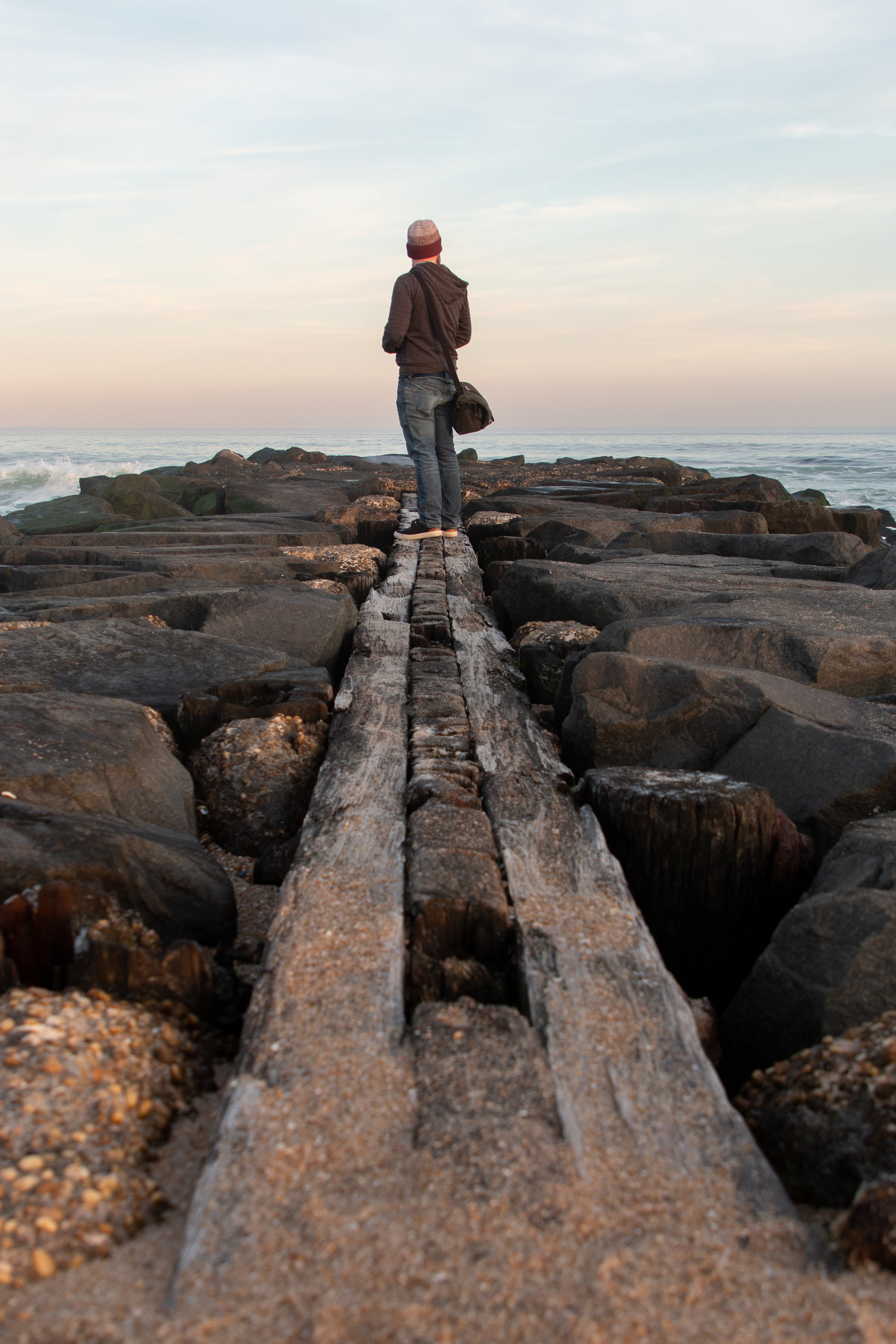 Man standing on rocks in Asbury Park, New Jersey. Photo by Kayleigh Ann Archbold.