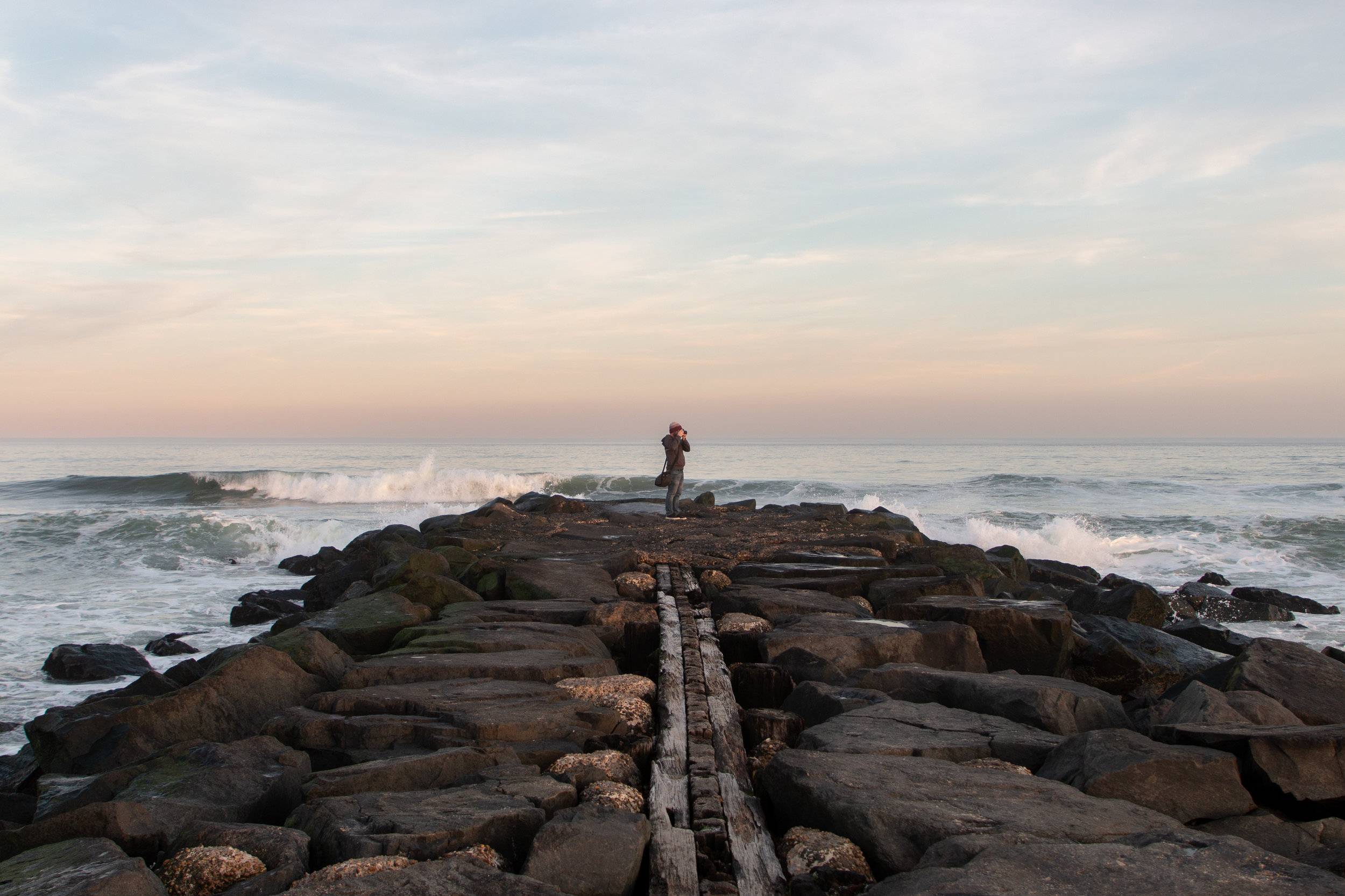 Man standing on rocks at sunset in Asbury Park, New Jersey. Photo by Kayleigh Ann Archbold.