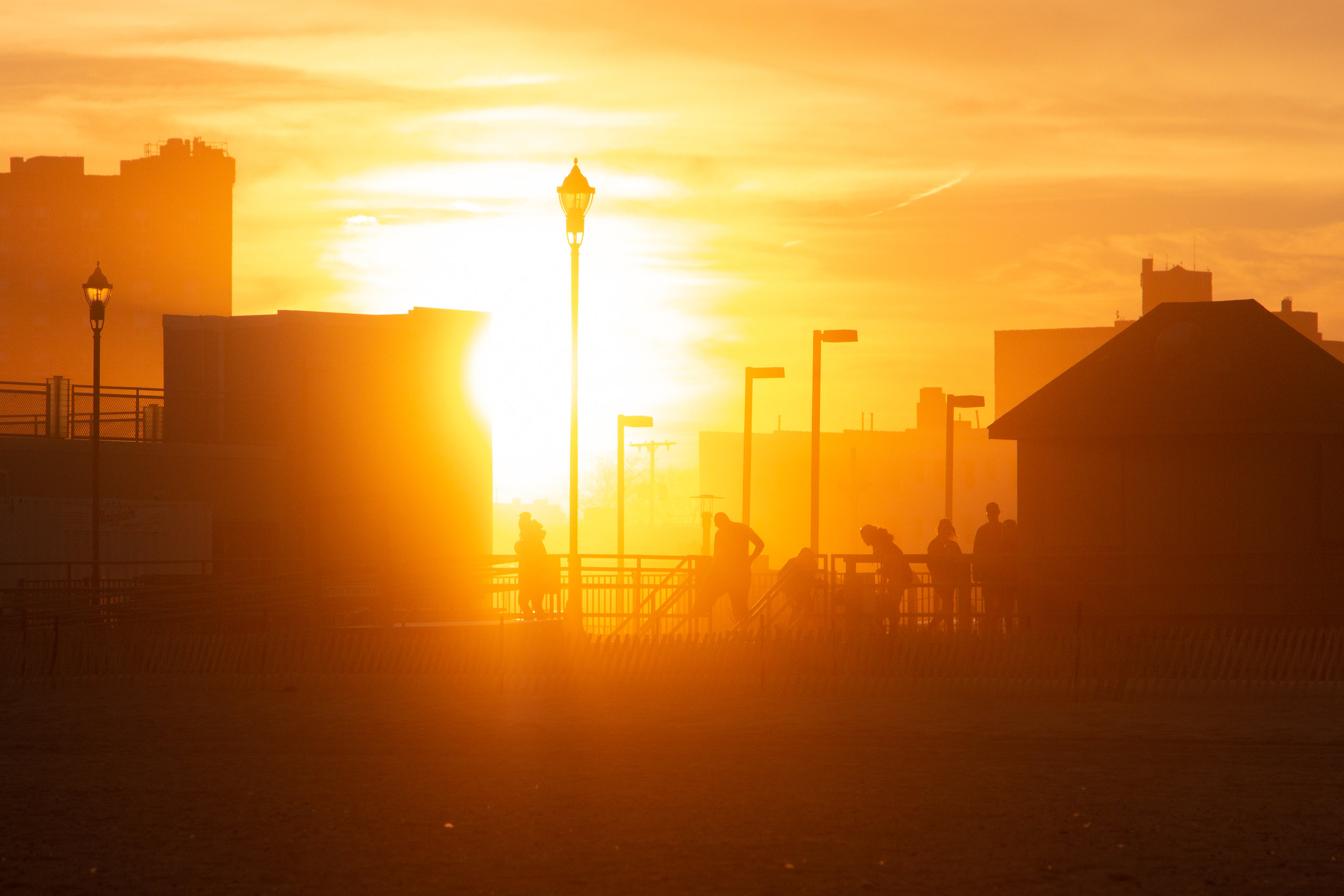 People on boardwalk at sunset in Asbury Park, New Jersey. Photo by Kayleigh Ann Archbold.