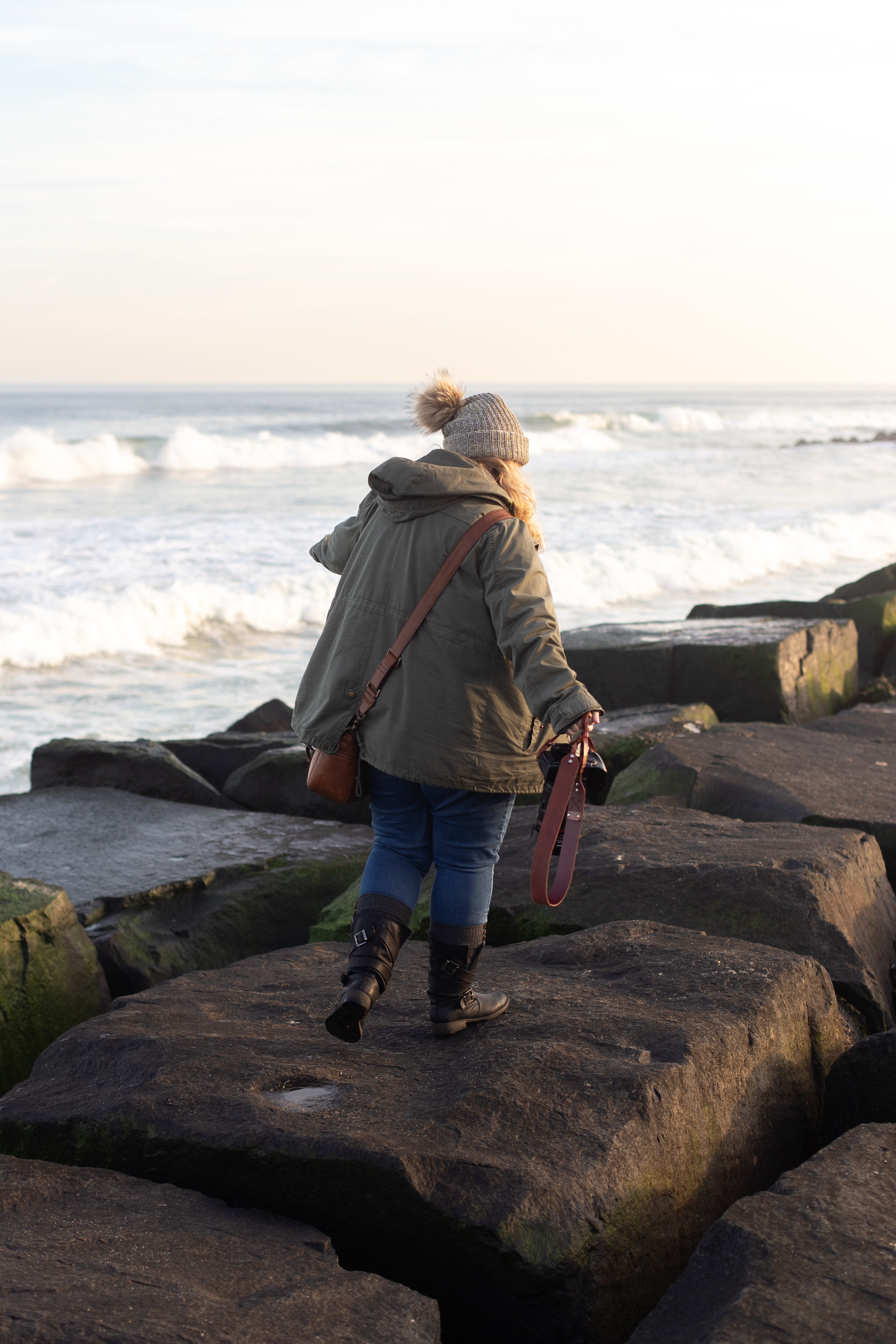 Woman standing on rocks in Asbury Park, New Jersey. Photo by Kayleigh Ann Archbold.
