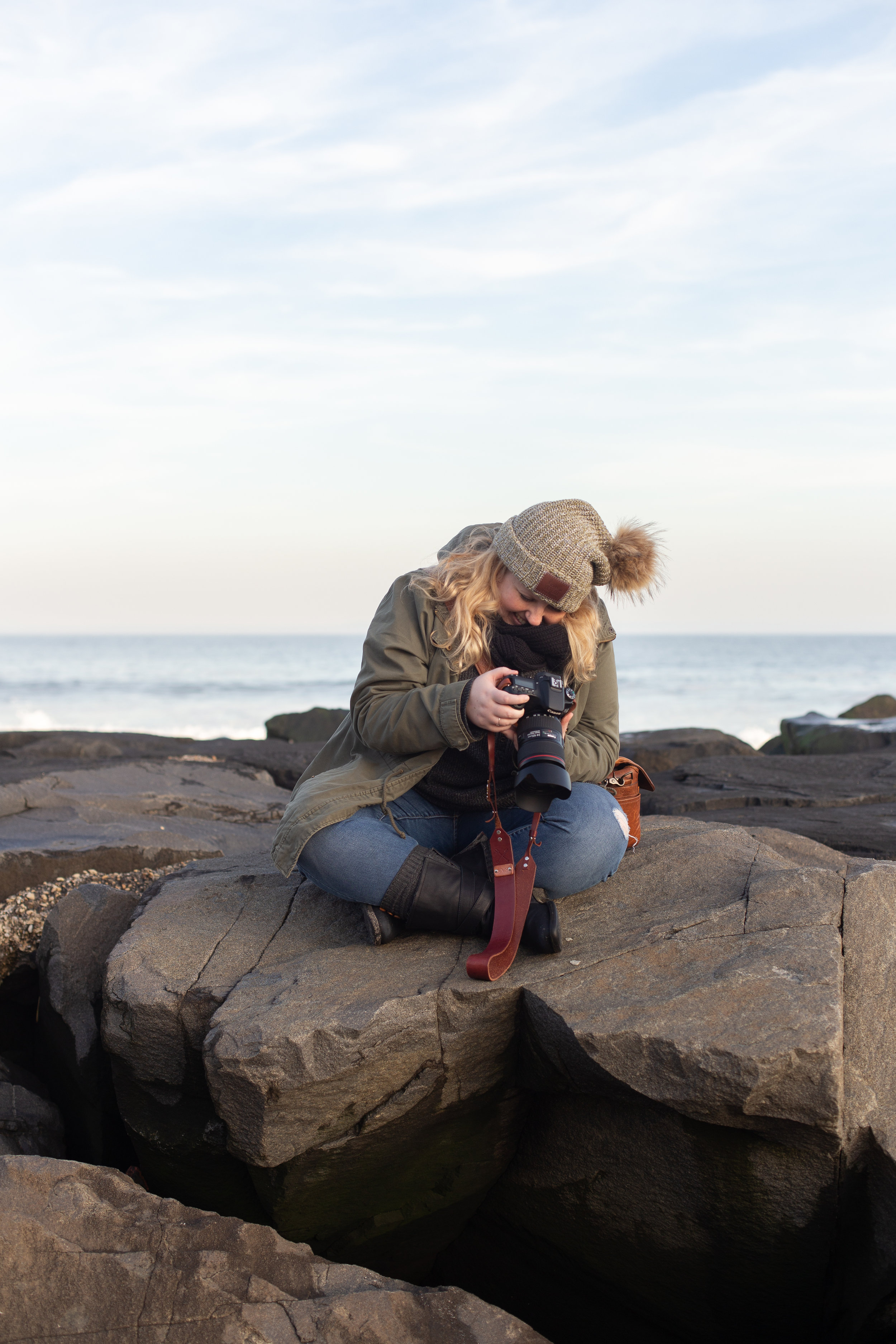 Woman sitting on rocks in Asbury Park, New Jersey. Photo by Kayleigh Ann Archbold.