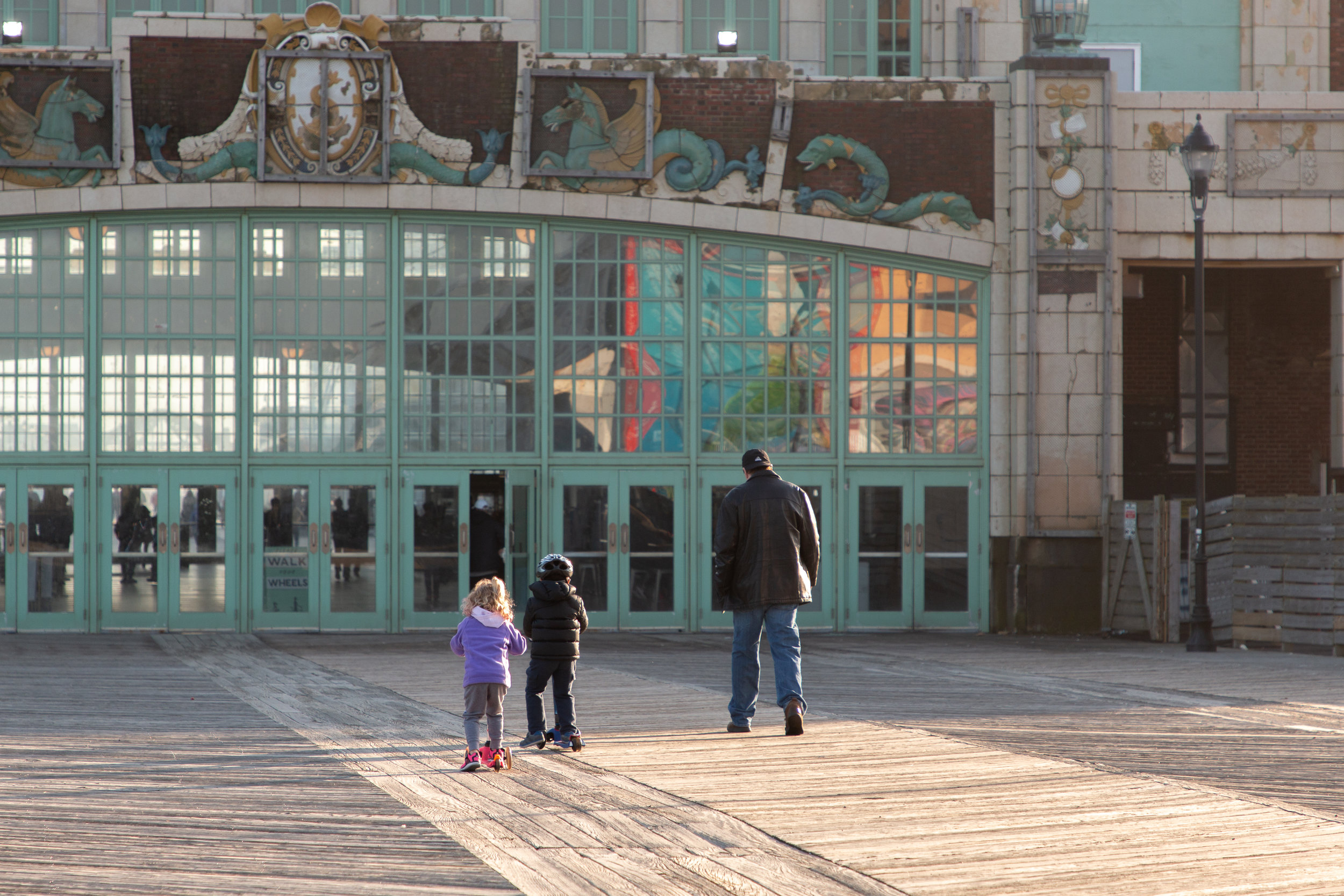 Man and two kids on boardwalk in Asbury Park, New Jersey. Photo by Kayleigh Ann Archbold.