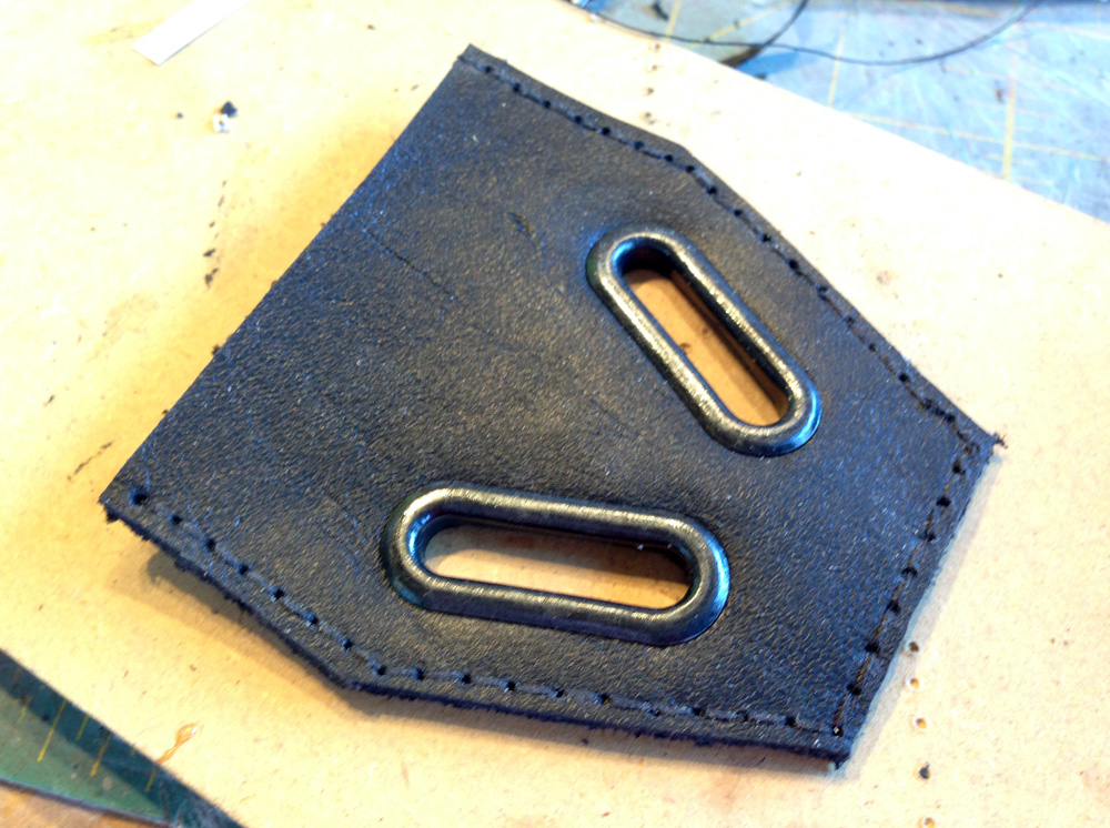 Shortly after, I decided to completely replace the entire piece at the bottom of the shoulder armor. I cut and stitched a new leather piece to replace the vinyl one, added accurate metal grommets and transplanted my accurate tabs.