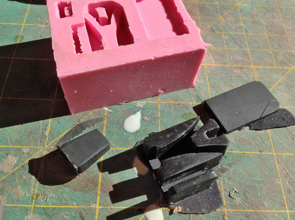 By looking at photos of screen used props and other people's cuff builds, I built the parts for the zip cuffs and made a mold of them. The cuff mechanism consists of an end cap, the cuff lock box and a cover plate. Here is an Onyx cast resin copy.