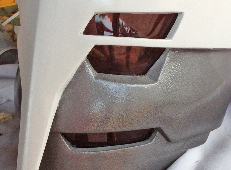 The lenses were backed with mirrored window tint so hide the eyes inside and then were attached with hot glue.