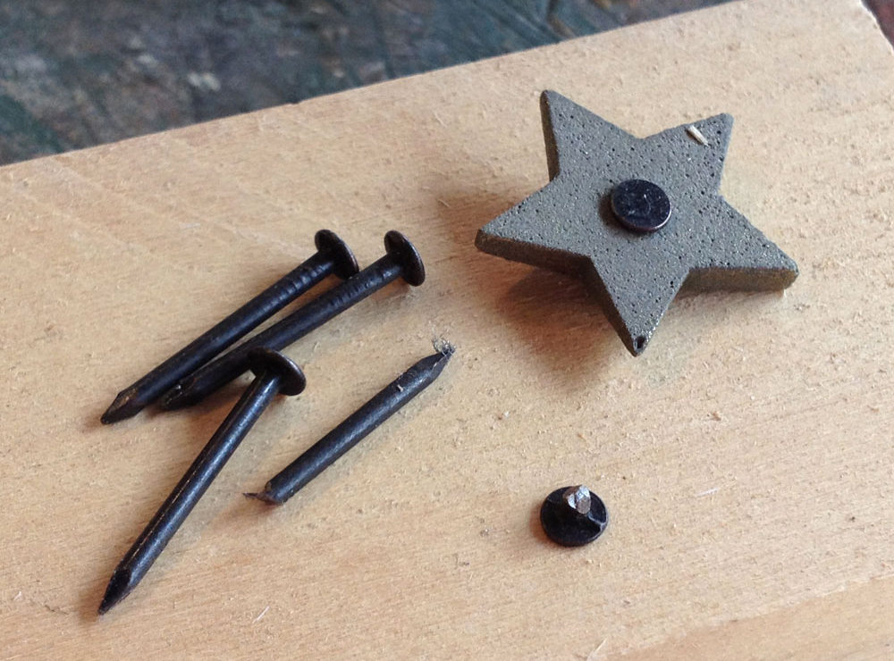 Each star had a hole drilled in the back so that a nail head could be glued in place.