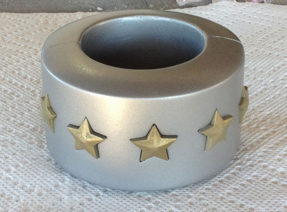 The cuff was painted with several light coats of Rustoleum Hammered Silver. The light coats give you a durable metallic finish without the hammered look. The final stars are in place but apparently not oriented in their holes correctly in this picture.