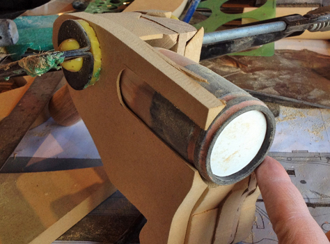 I started fleshing out the pistol grip with MDF, carving out a recess for the chamber cylinders.