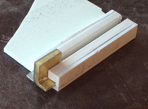 """To make a sliding switch (for what we assumed was a safety), I glued two """"L""""-shaped pieces of metal together and made a styrene rail for it to slide along."""