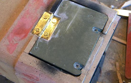 I attached the battery door with a small brass hinge. I cut a recess in the door and end cap to hide the hinge.