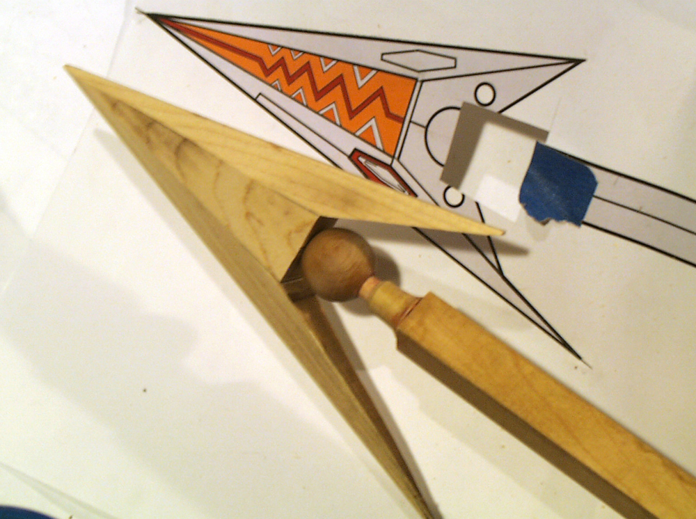 I inserted a threaded rod into the end of the shaft to hold the tail parts. The arrowhead was cut from a solid piece of maple, the ball is a wooden drawer handle and the part under it was turned from dowel.
