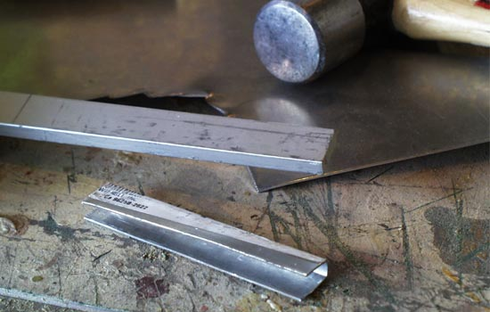 I formed the magazine release by hammering aluminum sheet around a steel bar.
