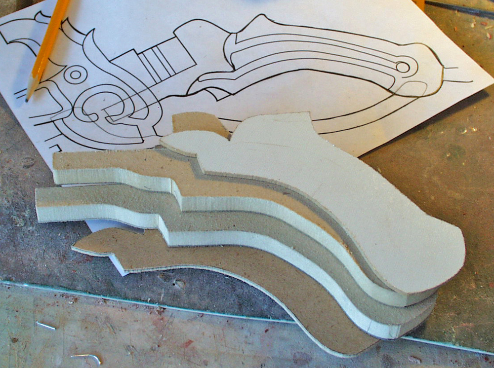 The grip was cut from 1/2″ MDF with 1/8 MDF grip plates. In order to later insert the trigger and other parts, I needed to be able to split it in half.