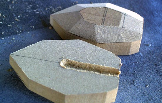 I cut the pommel piece from two layers of MDF and a channel for the rod. The facets were shaped on a belt sander.