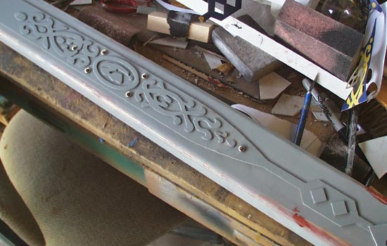 I wanted to make the design on the scabbard with more relief so I made a master from thicker styrene and used scrapbooking brads for the rivets