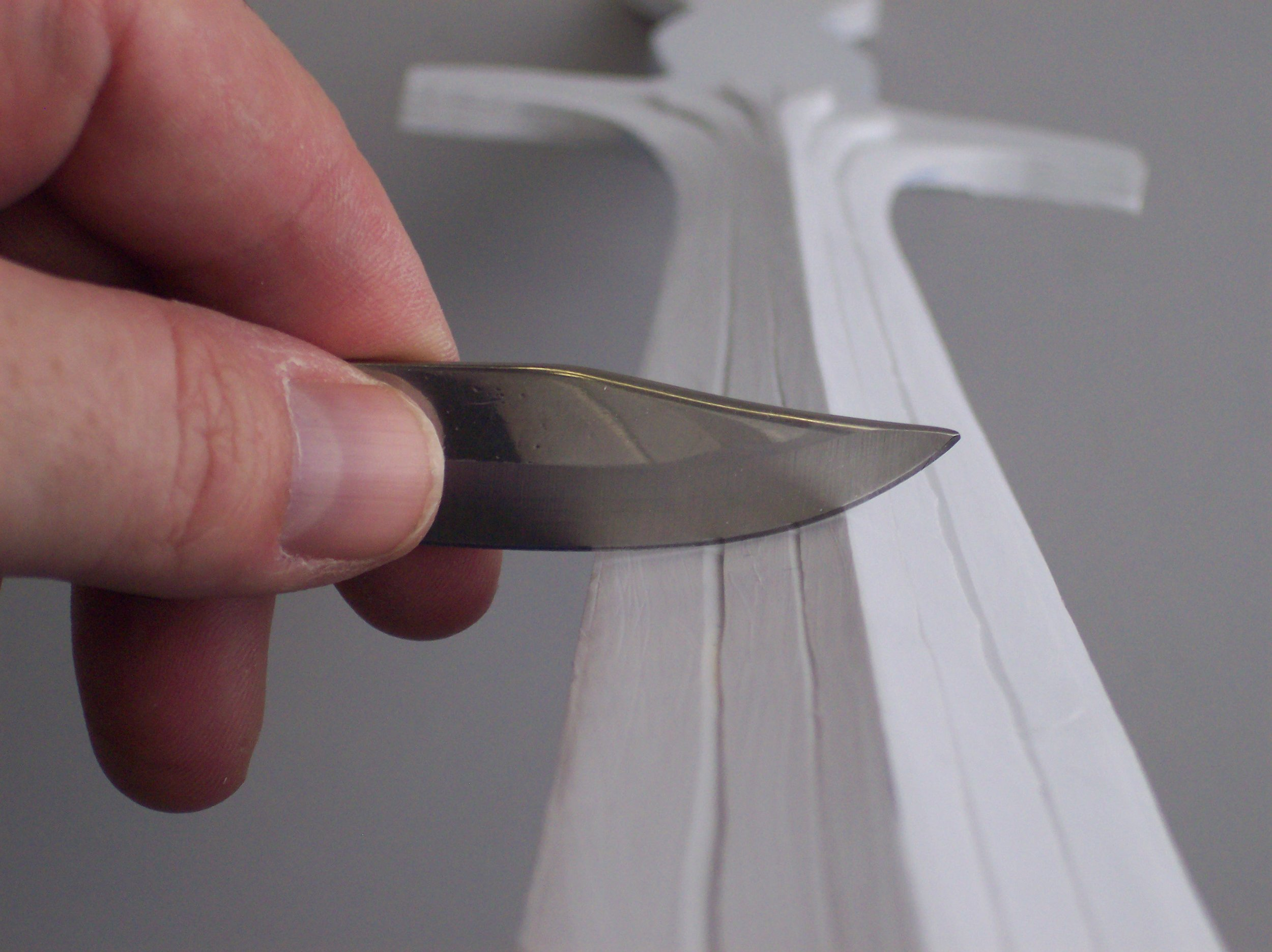 I used the long blade from my Swiss Army knife to shave a blade edge on the sword. Hold the knife's edge PERPENDICULAR to the surface of the plastic and you can shave the plastic into shape. This also works as a alternative to rough sanding.