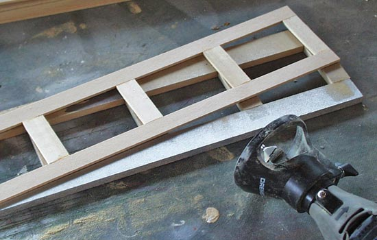 To add the interior router edge I had to build a jig for the router guide (1/4″ MDF) to rest against. I then glued each frame to a sheet of 3/32″ basswood (with the window areas cut out).
