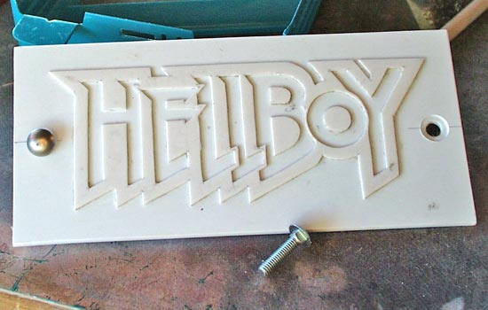 I wanted to make a nice logo plaque to mount on the base. I printed out the Hellboy comic logo in reverse, placed it face down on .060 styrene, wet it with lacquer thinner and burnished. When you remove the paper, a nice copy is magically applied to the plastic! I trimmed out the logo with an Xacto and glued it to heavy .090 styrene plastic. I found some cool bolts in the junk can and drilled holes in the plaque for them.