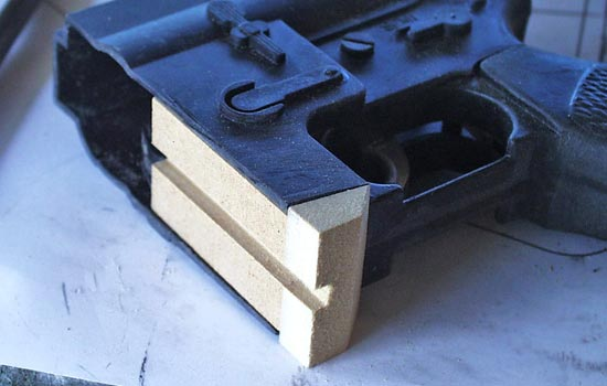 The stock, handle/sight and half of the magazine were hack sawed off the toy to make room for the new parts. A plug of MDF was glued into the magazine well for rigidity and to guide the new magazine.