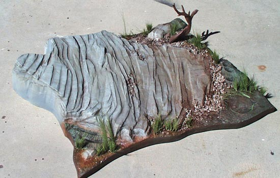I added model railroad gravel to the base of the cliff and little bits in crevasses. I watered down Elmers glue and sprayed it over the gravel to lock it in place. I added some railroad grass (very fine green threads that you cut to size) to the base as well as a dead tree that I recently discovered in a box.