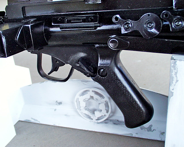 "The prop has a working trigger and safety, which took some figuring out as the ""forward"" position is ""FIRE"" and the ""vertical"" position is ""SAFE"". The trigger has a small spring pushing it forward and the safety employs a double lever that blocks the trigger when on SAFE. The pistol grip itself is a resin copy from a REAL Sterling, I bought from a guy at the Blaster Builders Club."