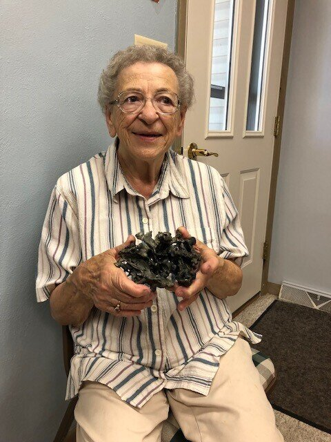 Jane Mleziva, long-time St. Thomas the Apostle parishioner, with a fragment of the bell tower that remains from the St. Hubert fire of 1966.