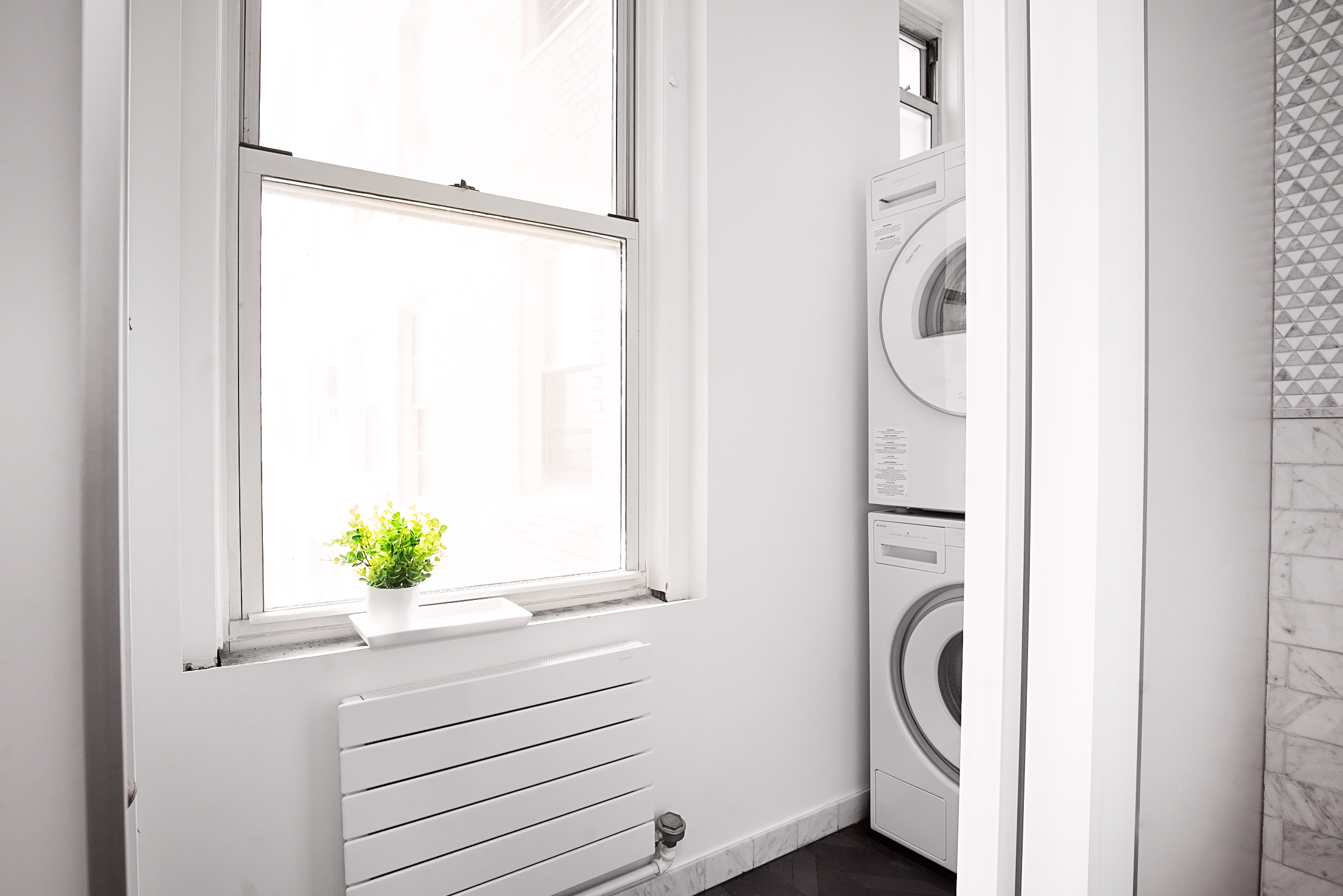 With a slim footprint that took very little space in a luxurious bathroom, we created a fully functional yet hidden laundry room.
