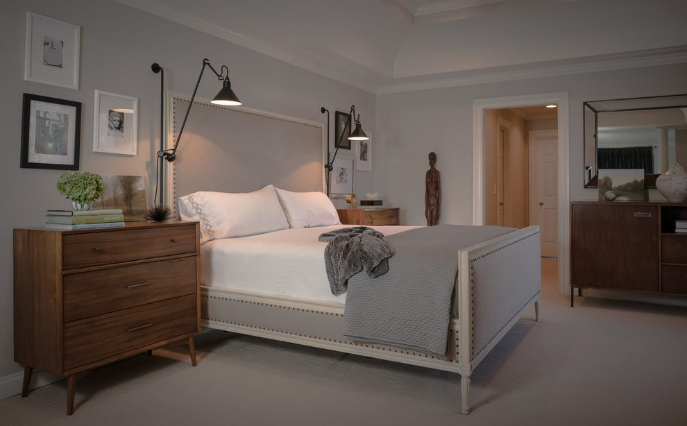 A transitional modern bedroom with soft grey, tufted /studded headboard with ultra-modern bedside lamps in black. Bedroom by  Beckwith Interiors .
