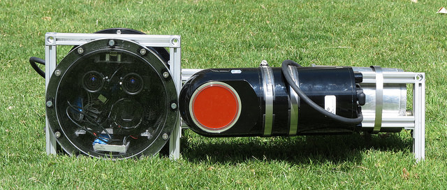 Underwater Stereo Camera system developed for mapping underwater structures. The main pressure housing contains a stereo pair of IDS machine vision cameras, a Microstrain Inertial Measurement Unit, and a Sony QX100 camera. On the right side of the image is a Doppler Velocity Log used for acoustic bottom tracking.