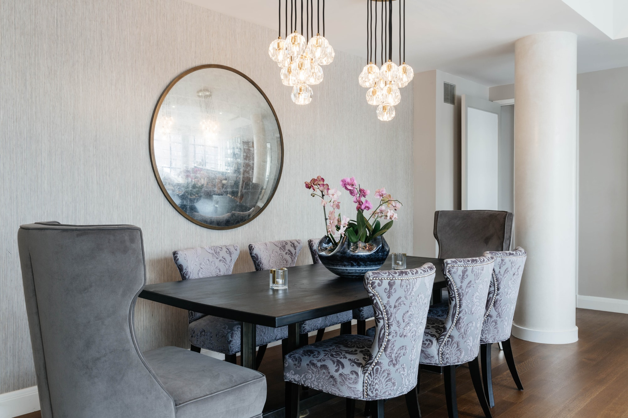 Dining room space with convex mirror hanging on wall